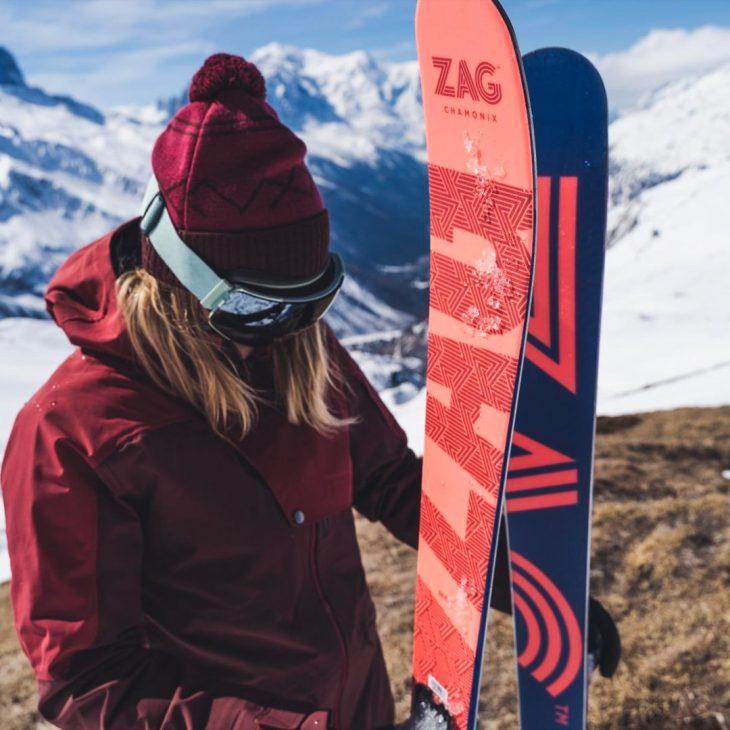 Skieuse aux cheveux blonds et combinaison rouge en pleine montagne, tenant une paire de skis Zag rouge et bleue