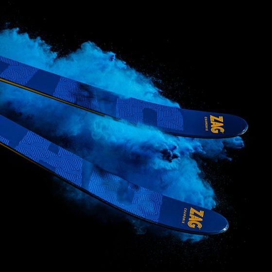 Paire de skis bleus Zag Skis sur fond noir, comme glissant sur une poudre bleue dynamique
