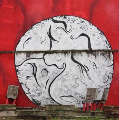 Graffiti d'une lune pensive sur un mur rouge